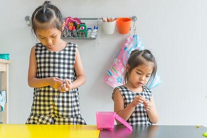 Cute little girl threading beads and mak