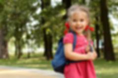 Beautiful little girl with backpack walk