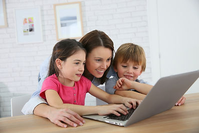 Mother with kids playing on laptop compu