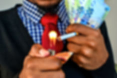 Man lighting cigarette with Money (Rands