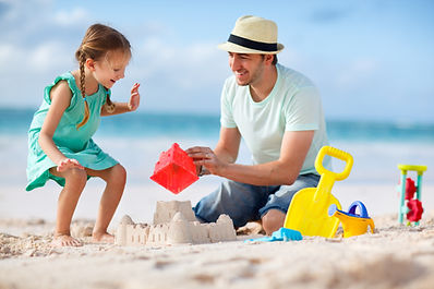 Father and daughter on beach building sa