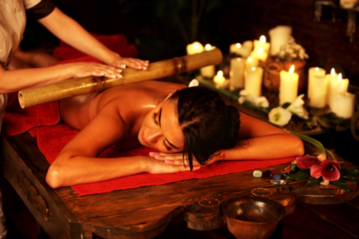 Bamboo massage of woman in spa salon. Gi