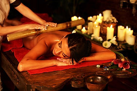 Bamboo massage of woman in spa salon. Gi