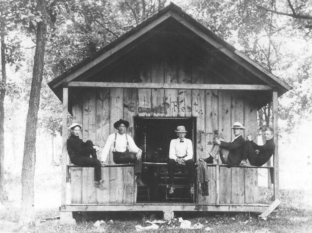William Harley (2º da esquerda), Walter Davidson (4º da esquerda) e Arthur Davidson (extrema direita) na varanda de sua cabana no Lago Ripley em Wisconsin. C. 1915.  Arquivo da Harley-Davidson Motor Company. Copyright H-D.®