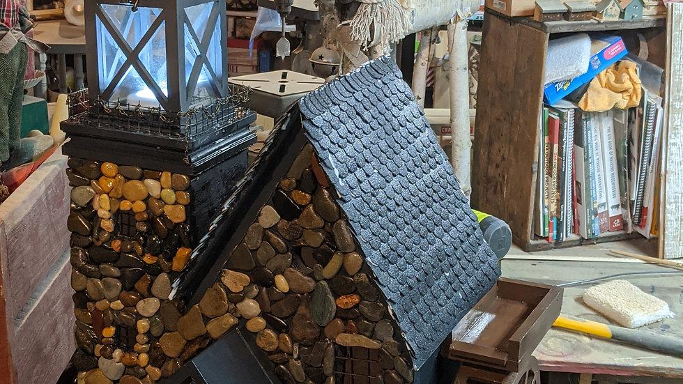 Rock birdhouse with waterwheel