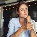 Woman drinking coffee reflecting on the