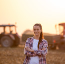 Young woman farmer in field with tractor
