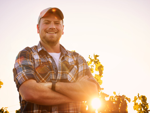 Farmer smiling in plaid shirt in sunset.
