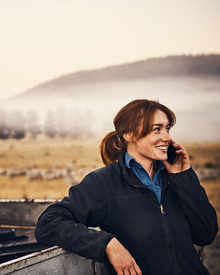 Woman farmer on the phone in the field.j
