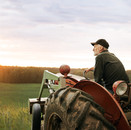 Farmer sitting on old loader tractor in