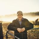 Woman farmer in the field leaning on gat