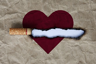 Cigarette burning brown paper with heart