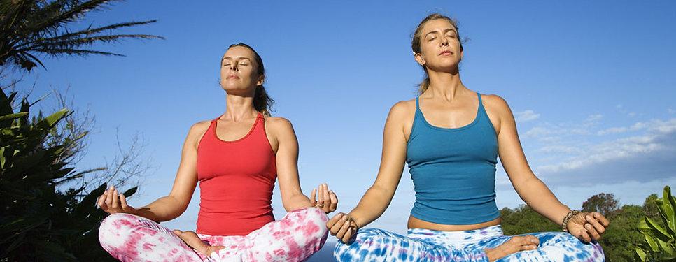 Photo de deux femmes effectuant une séance de yoga en extérieur pour illustrer les activités sportives proposés par le Gym Club Genay
