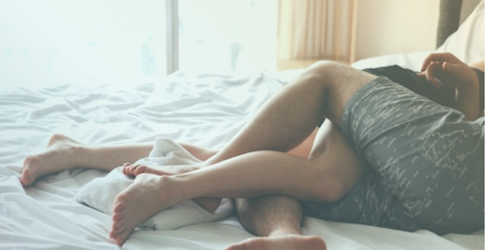 A couple laying in bed with their legs intwined.