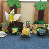 A collection of cardboard dinosaurs and cardboard trees