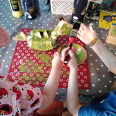 2 children paint a cardboard dinosaur