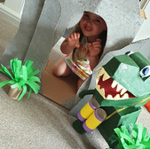 Child roars next to cardboard dinosaur and cave