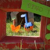 Cardboard dinosaur hatching form an egg framed by a cardboard 'Dino TV' frame