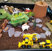 Cardboard dinosaur in a child made dinosaur landscape made from toys