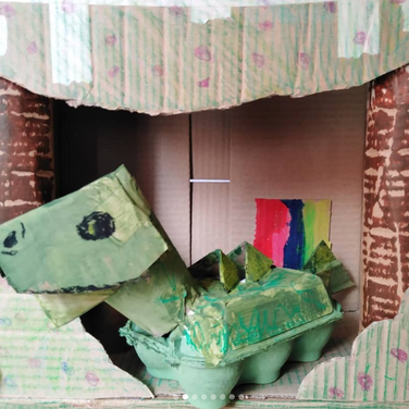 a completed Cardboard Dinosaur sits in a cardboard cave