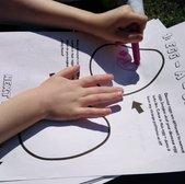 Child drawing on a dinosaur worksheet
