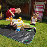 2 children build a cardboard dinosaur in a garden