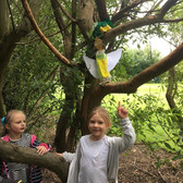 2 children point to cardboard dinosaurs in a real tree