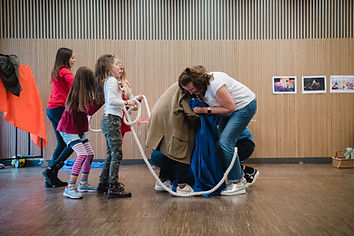 Family's play together with rope and costumes at The National Theatre