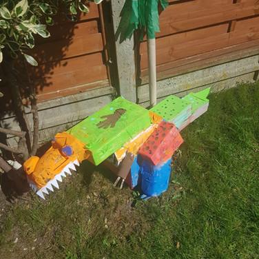A large cardboard dinosaur in a garden