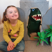 Child smiles next to cardboard dinosaur and cave
