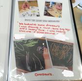 Nursery record book of children drawing chalk dinosaurs