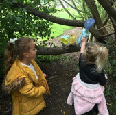 2 young children position a cardboard Dinosaur in a real tree
