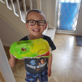 Child smiles holding craft dinosaur head