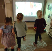 3 children stand on bubble wrap watching a dinosaur film