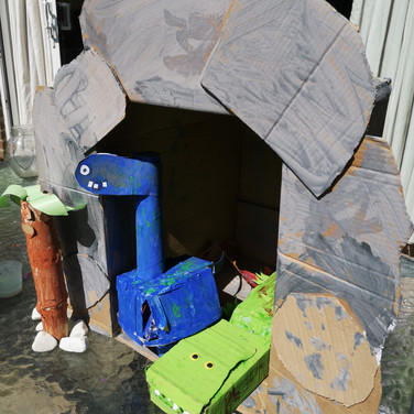 2 Cardboard dinosaurs, sit in a cardbaord cave