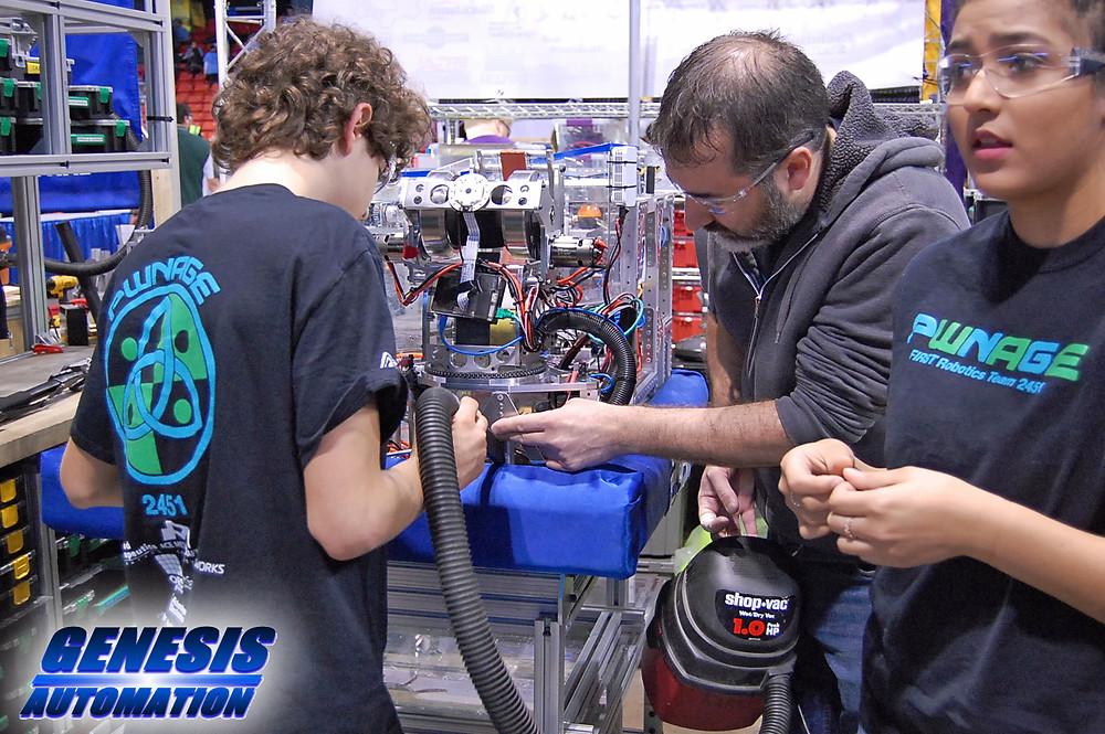 FIRST Robotics Team PWNAGE #2451 members building a robot
