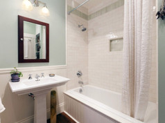 Bathroom with clean white tile and soft blue walls