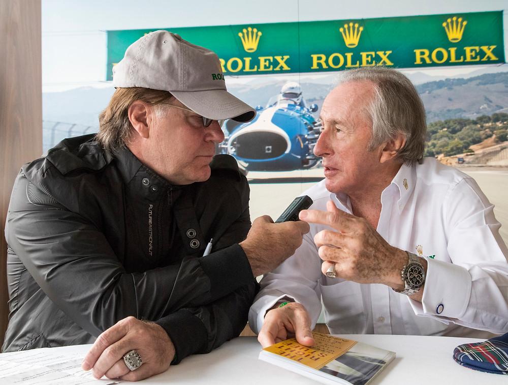 Adventure journalist Jim Clash (left) interviews Formula One racing legend Sir Jackie Stewart (right).