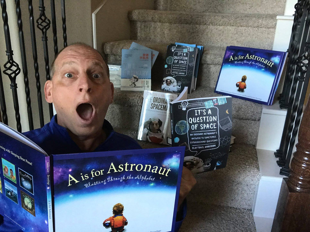 """Retired NASA astronaut Clayton C. Anderson at home showing off his books: """"The Ordinary Spaceman,"""" """"A is for Astronaut"""" and """"It's a Question of Space.""""  Photo © Clayton C. Anderson."""