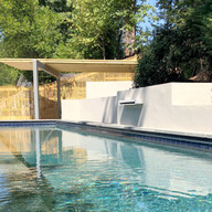 Modern geometric swimming pool with spillover, stucco wall and autocover