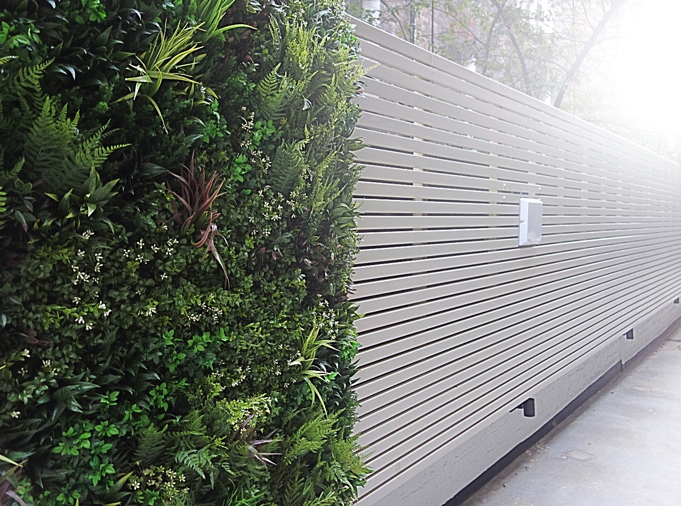 A white fence decorated with vegetation.
