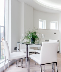 A dining table with a glass top with white chairs surrounding it.