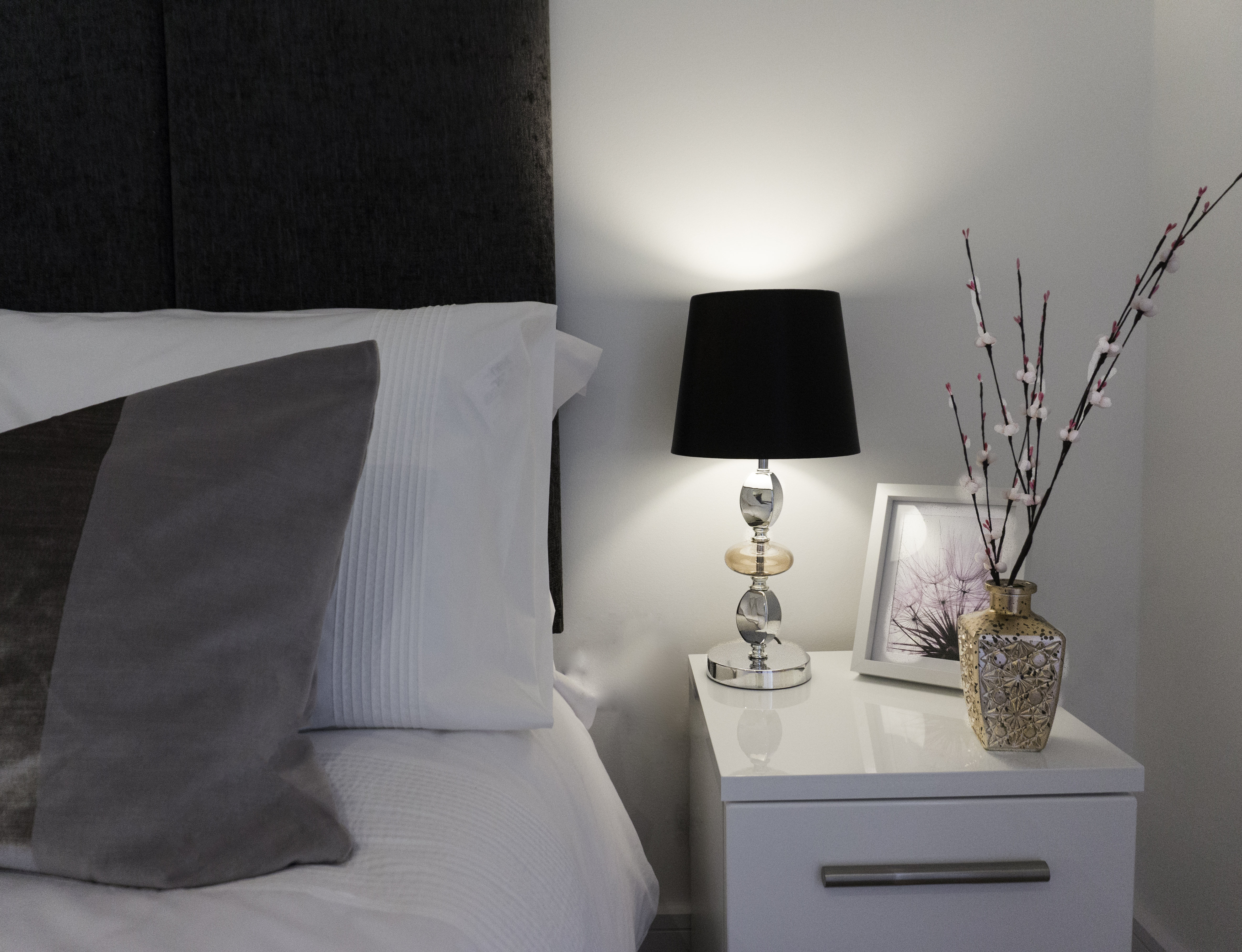A white bed and bedside table.