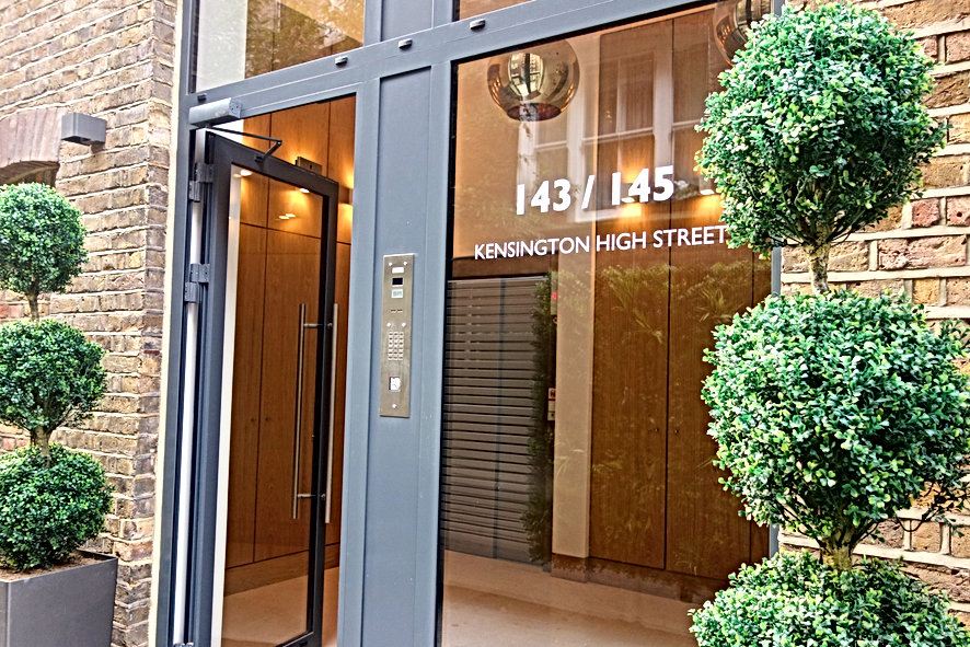 A front entrance to a luxury development of flats in 143/145 Kensington High Street.