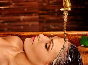 Young woman having pouring oil massage i