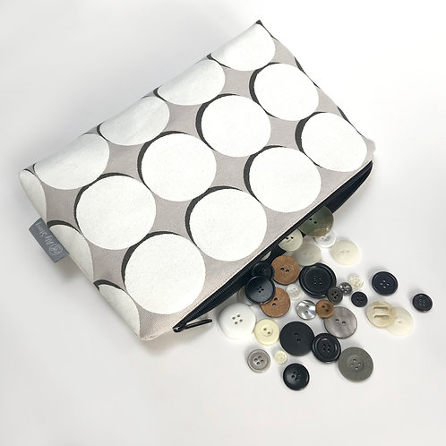 White circle with black eclipse patterned cosmetic bag
