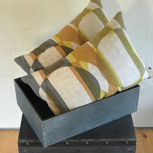 two oblong cushions in a black trug