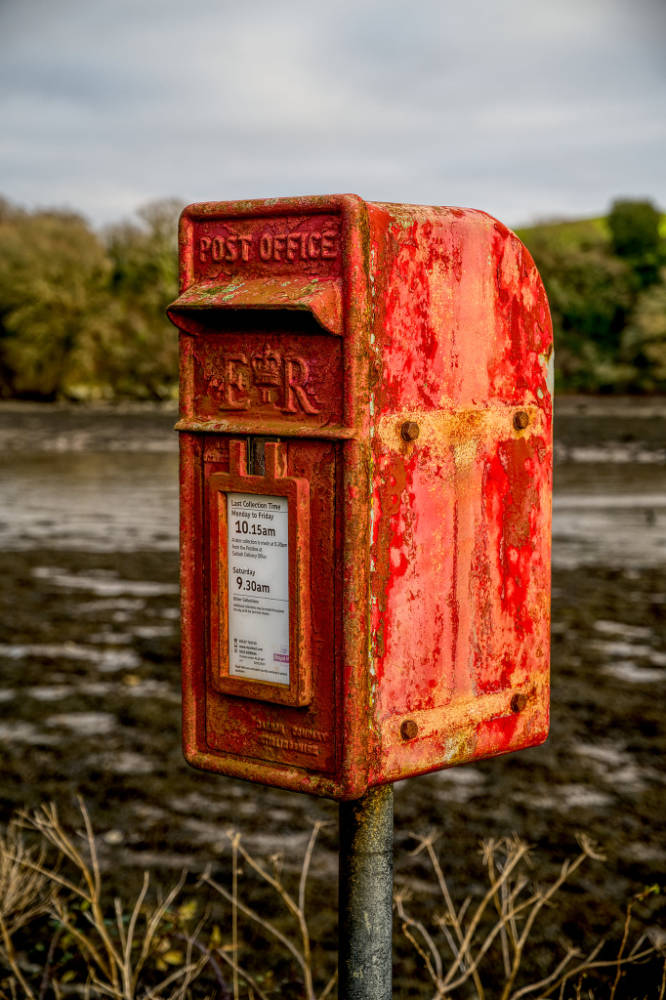Weathered red post box