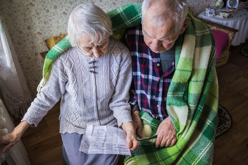 Cold old couple looking at bills.jpg