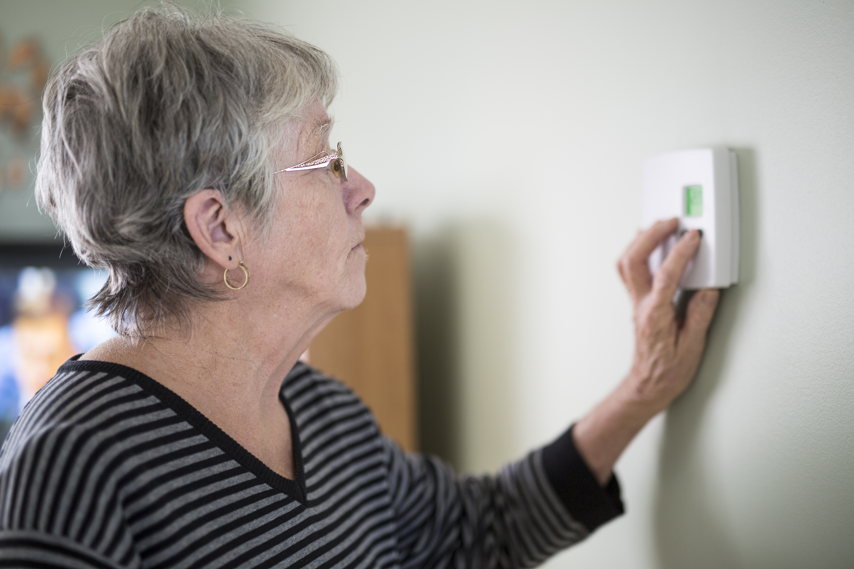 Lady adjusting thermostat